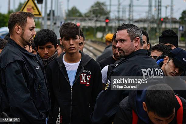 Refugees wait to be registered by the German federal police at the railway station on September 14 2015 in Freilassing Germany German authorities...