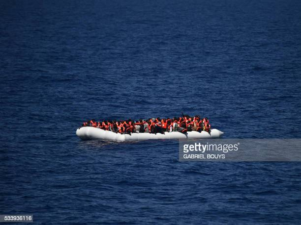 TOPSHOT Refugees wait to be rescued during an operation at sea with the Aquarius a former North Atlantic fisheries protection ship now used by...