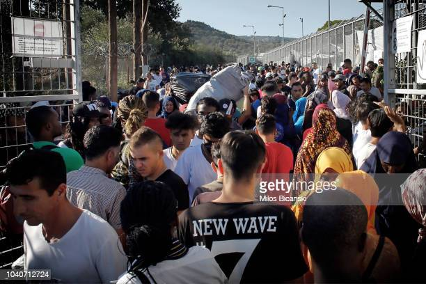 Refugees wait to board a bus which will take them to port of Mytilene where they plan to board a ferry to Athens at Moria Refugee Camp on September...