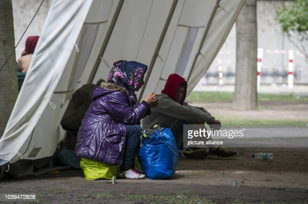Refugees wait under tents on the premises of the Berlin State Office for Health and Social Affairs in Berlin Germany 09 July 2015 The chairwoman of...