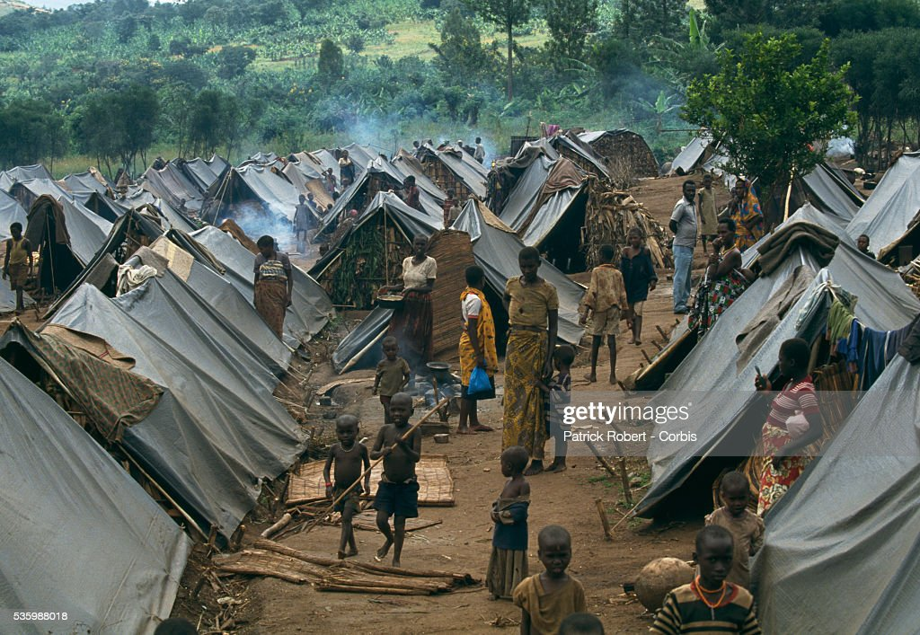 Refugees walk among the tents in a refugee camp for Tutsis near Kirundo in northern Burundi. The camp was created for refugees entering the country from Rwanda due to the inter-ethnic civil war. In April 1994, civil conflict broke out in Rwanda between Hutus and Tutsis, the two major ethnic groups in Burundi and Zaire, leading to widespread genocide in Rwanda. During the war, approximately 63,000 refugees (mainly Tutsi) poured into northern Burundi. | Location: Near Kirundo, Burundi.