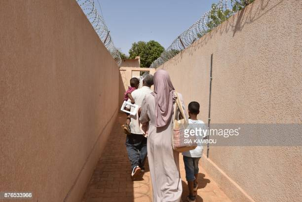 Refugees walk at a UNHCR building in Niamey on November 17 after they were evacuated from Libya and after interviews by protection officers of the...