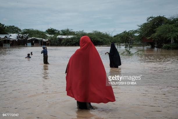 Refugees walk in floodwaters after a heavy rainy season downpour at the Dadaab refugee complex, in the north-east of Kenya, on April 17, 2018. - The...