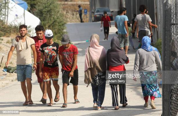 Refugees walk through the Moria refugee camp on May 20 2018 in Mytilene Greece Despite being built to hold only 2500 people the camp on the Greek...