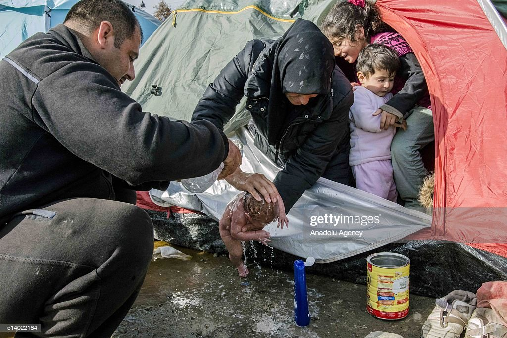 Refugees wash a new born baby as they stay in tents that they set up in the Idomeni town in Greece, near the Macedonian border on March 6, 2016.
