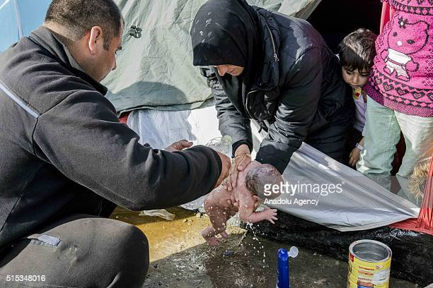 Refugees wash a new born baby as they stay in tents that they set up in the Idomeni town in Greece near the Macedonian border on March 6 2016