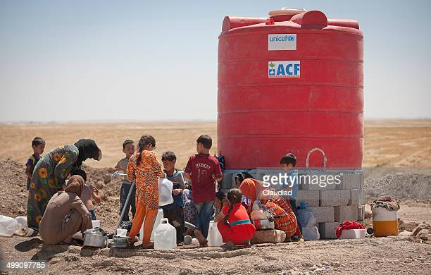 refugees washing cloth - humanitarian aid stock pictures, royalty-free photos & images