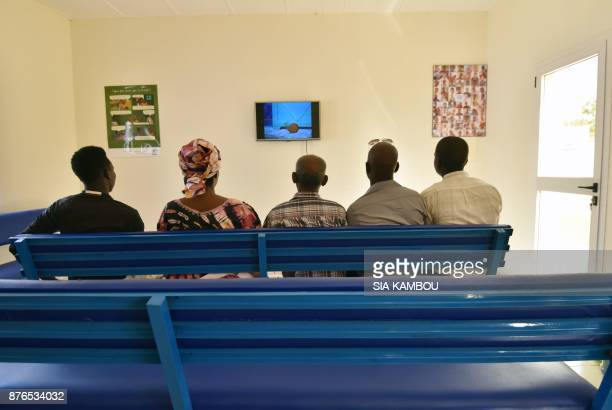 Refugees watch television at a UNHCR building in Niamey on November 17 after they were evacuated from Libya and ahead of interviews by protection...