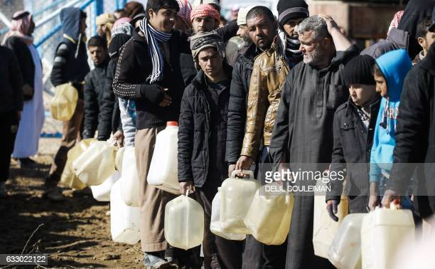 TOPSHOT Refugees who fled the Iraqi city of Mosul due to the fighting between government forces and Islamic State group jihadists queue for heating...