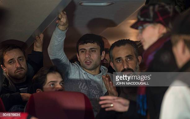 Refugees who have been granted asylum status in Germany speak to officials in a bus in front of the chancellery in Berlin on January 14 after it...