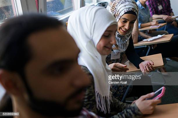 Refugees who have received asylum status in Germany attend a panel discussion about classes to help them prepare for a study program at the Freie...