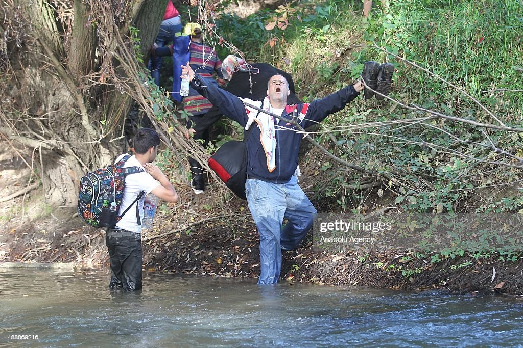 Refugees who try to go to the capital Ljubljana on foot walk in the Sutla river in Brezice, Slovenia on September 18, 2015. Slovenia intends to reinforce its border with Croatia to prevent a possible influx of migrants seeking a new route into Europe.