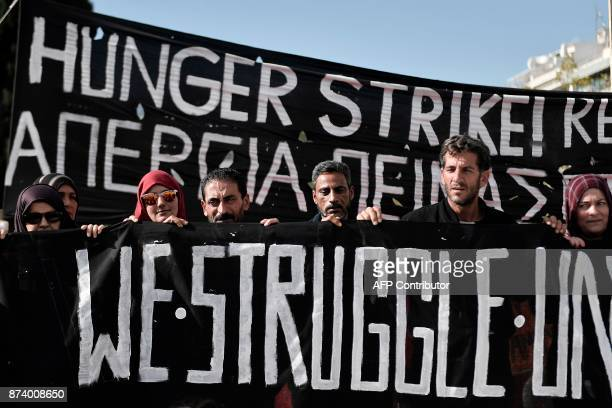 TOPSHOT Refugees who were on hunger strike for 14 days to demand a faster family reunification process in Germany hold a banner as they demonstrate...
