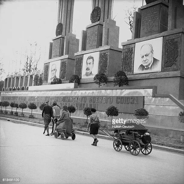Refugees with all of their belongings pass a war memorial depicting the Big Three Berlin July 12 1945