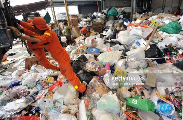 Refuse collector employees unload recyclable garbage at La Alqueria Recycling Center in Bogota Colombia on January 17 2013 Some 60 recyclers classify...