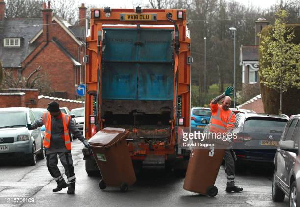 Refuse collectors acknowledge the applause from local residents as waste bins are collected on March 30, 2020 in Northampton, England. The...