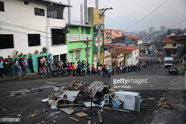 Refuse from a barricade put up by protesters clutters the street in front of a long queue to buy basic foodstuffs at a supermarket before sunrise on...