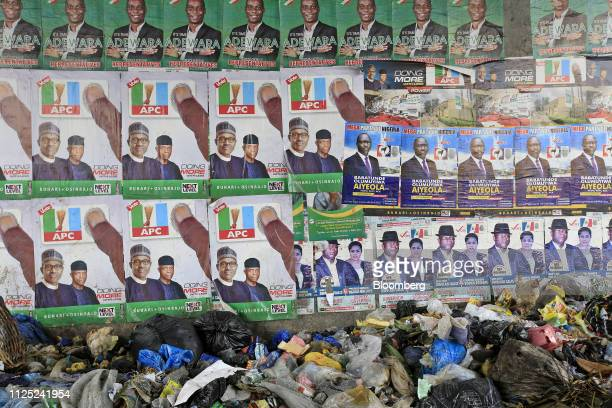 Refuse sits under campaign posters including Muhammadu Buhari Nigeria's president and candidate of the ruling All Progressives Congress party left in...