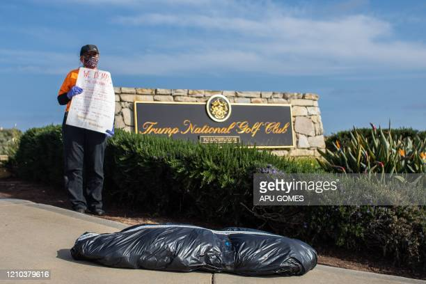 RefuseFascism supporter wearing a mask and gloves as a preventive measure against the spread of COVID-19 stands near a symbolic home-made body-bag in...