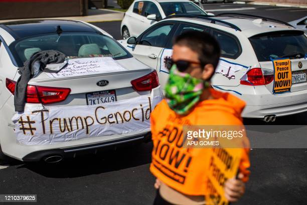 A RefuseFascism supporter wearing a mask as a preventive measure against the spread of COVID19 holds a sign in front of the Trump National Golf Club...