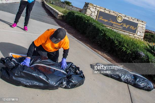 A RefuseFascism supporter wearing gloves as a preventive measure against the spread of the COVID19 places a symbolic homemade bodybag in front of the...