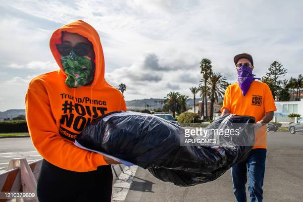 RefuseFascism supporters wearing scarves as a preventive measure against the spread of the COVID19 deliver a symbolic homemade bodybag in front of...