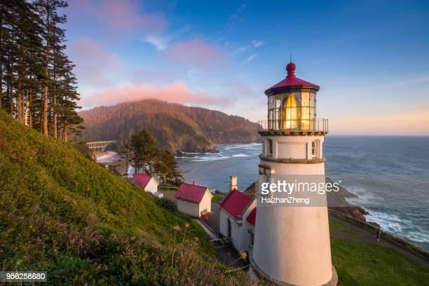 regal view heceta head lighthouse shining across oregon coast - oregon stock photos and pictures