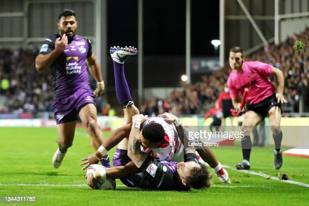Regan Grace of St Helens goes over to score their side's first try whilst under pressure from Richie Myler of Leeds Rhinos during the Betfred Super...