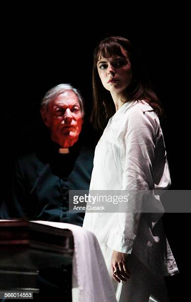 Regan MacNeil played by Emily Yetter walks in a trance as Father Merrin played by Richard Chamberlain looks on for a review of 'The Exorsist' at the...