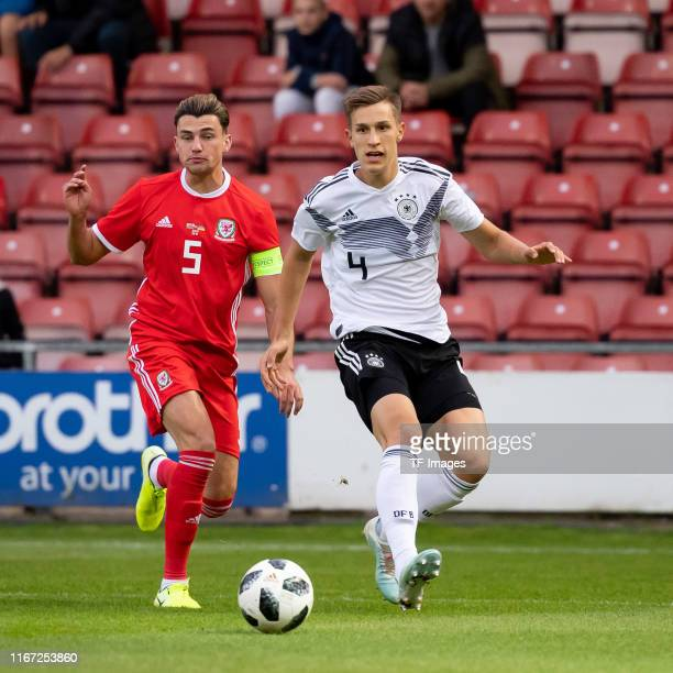 Regan Poole of Wales and Nico Schlotterbeck of Germany battle for the ball during the international friendly match between U21 Wales and U21 Germany...