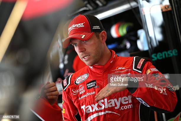 Regan Smith driver of the TaxSlayer Bowl Chevrolet stands in the garage area during practice for the NASCAR Xfinity Series Furious 7 300 at...