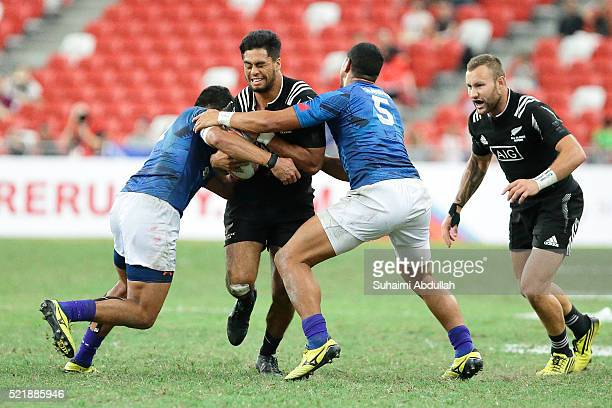 Regan Ware of New Zealand is tackled by Alex Samoa and Ed Fidow of Samoa during the 2016 Singapore Sevens Plate Final between New Zealand and Samoa...