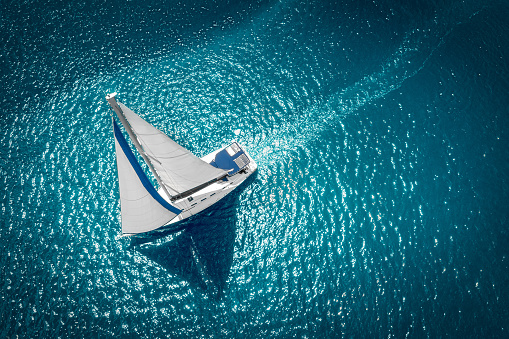 Regatta sailing ship yachts with white sails at opened sea. Aerial view of sailboat in windy condition 1151994519