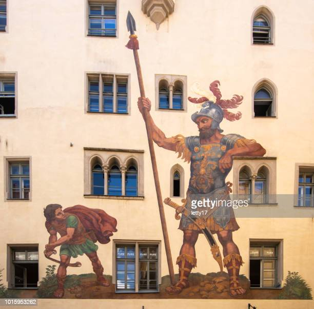 regensburg city. painting of david and goliath in middle of the old town. the building with the painting is called goliath building. - david and goliath stock photos and pictures