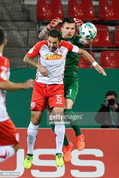Regensburg's Marco Gruttner heading the ball in front of Heidenheim goalkeeper Kevin Muller during the DFBCup soccer match between Jahn Regensburg...