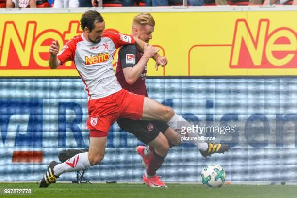 Regensburg's Sebastian Nachreiner and Nuremberg's Sebastian Kerk vie for the ball during the 2nd Bundesliga match pitting Jahn Regensburg vs 1. FC...