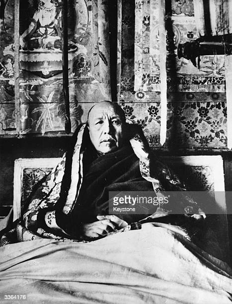 Regent of Tibet wrapped in shawls behind him an ornate wall hanging