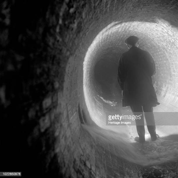 Regent Street Sewer Regent Street Westminster Greater London circa 1945circa 1980 A workman looking along the sewer by torchlight Artist Eric de Maré