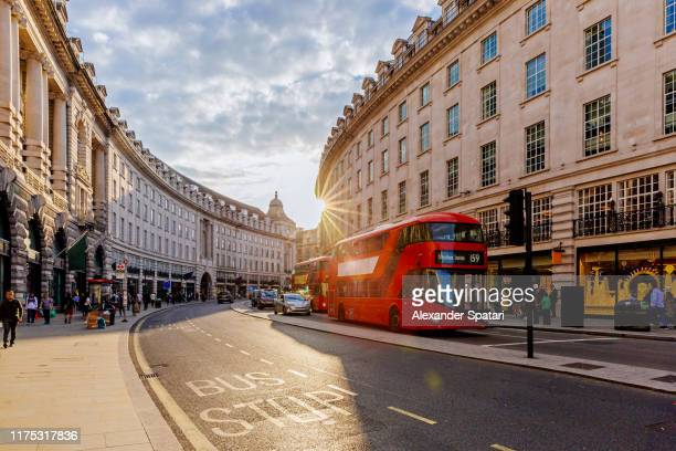 regent street  with sun shining through buildings during sunset, london, england, uk - london england stock-fotos und bilder