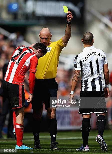 Regeree Howard Webb awards a yellow card to Yoan Gouffran of Newcastle, after a tackle on Adam Johnson of Sunderland during the Barclays Premier...