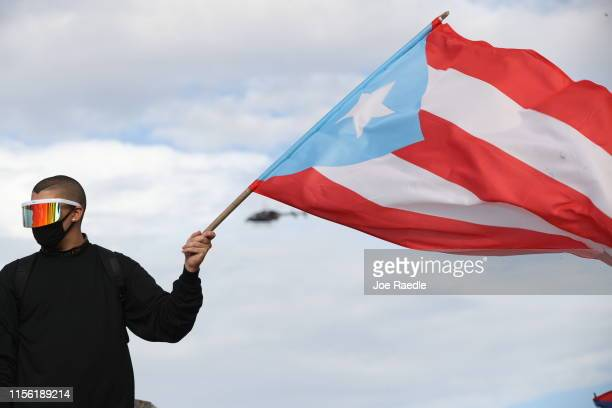 Reggaton singer and rapper Bad Bunny waves a Puerto Rican flag during protests against Ricardo Rossello the Governor of Puerto Rico on July 17 2019...