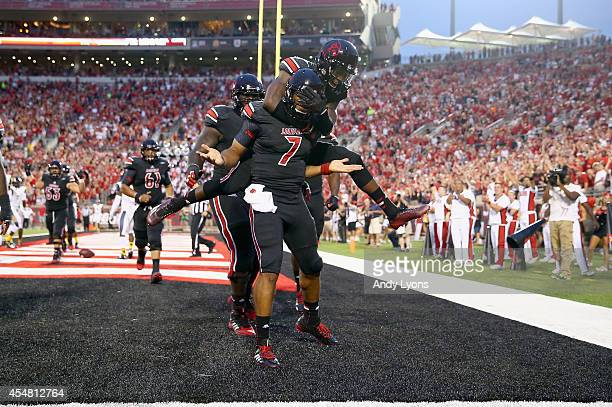 Reggie Bonnafon of the Louisville Cardinals celebrates with teammates after scoring a touchdown during the game against the Murray State Racers at...