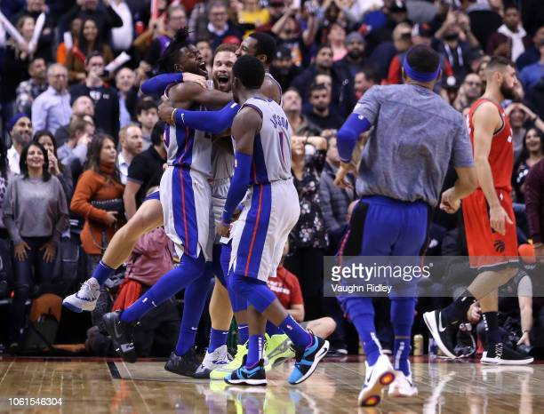 Reggie Bullock of the Detroit Pistons celebrates with teammates after sinking the winning basket during the second half of an NBA game against the...