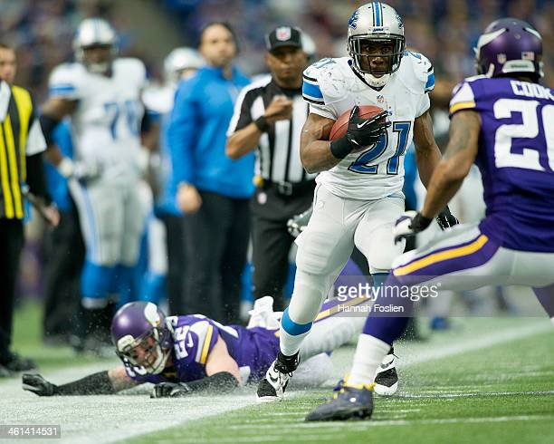Reggie Bush of the Detroit Lions carries the ball against Chris Cook of the Minnesota Vikings as teammate Chad Greenway looks on after a missed...