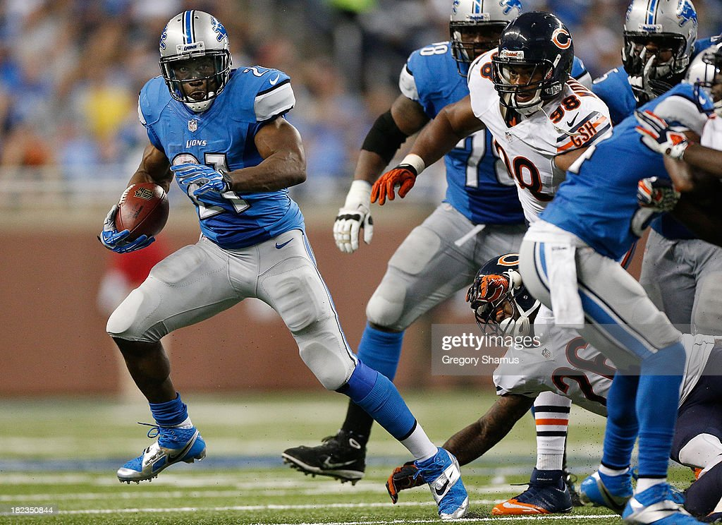 Reggie Bush #21 of the Detroit Lions looks for third quarter running room after getting away from Corey Wootton #98 and Tim Jennings #26 of the Chicago Bears at Ford Field on September 29, 2013 in Detroit, Michigan. Detroit won the game 40-32.
