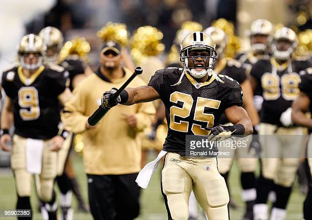 Reggie Bush of the New Orleans Saints carries a bat with him as he leads his teammates onto the field against the Arizona Cardinals during the NFC...
