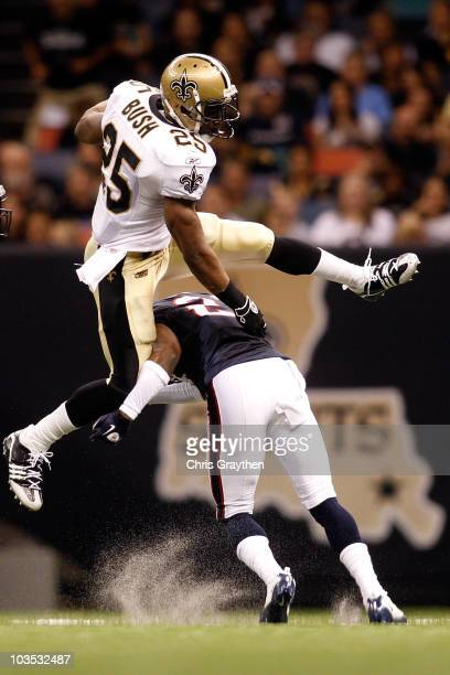Reggie Bush of the New Orleans Saints jumps over Brice McCain of the Houston Texans at the Louisiana Superdome on August 21 2010 in New Orleans...