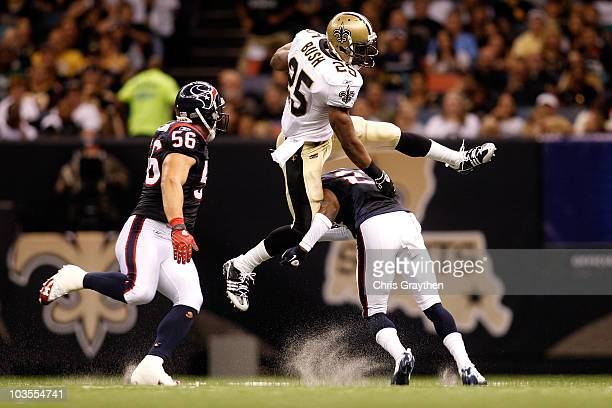 Reggie Bush of the New Orleans Saints jumps over Brice McCain of the Houston Texans at the Louisiana Superdome on August 21, 2010 in New Orleans,...