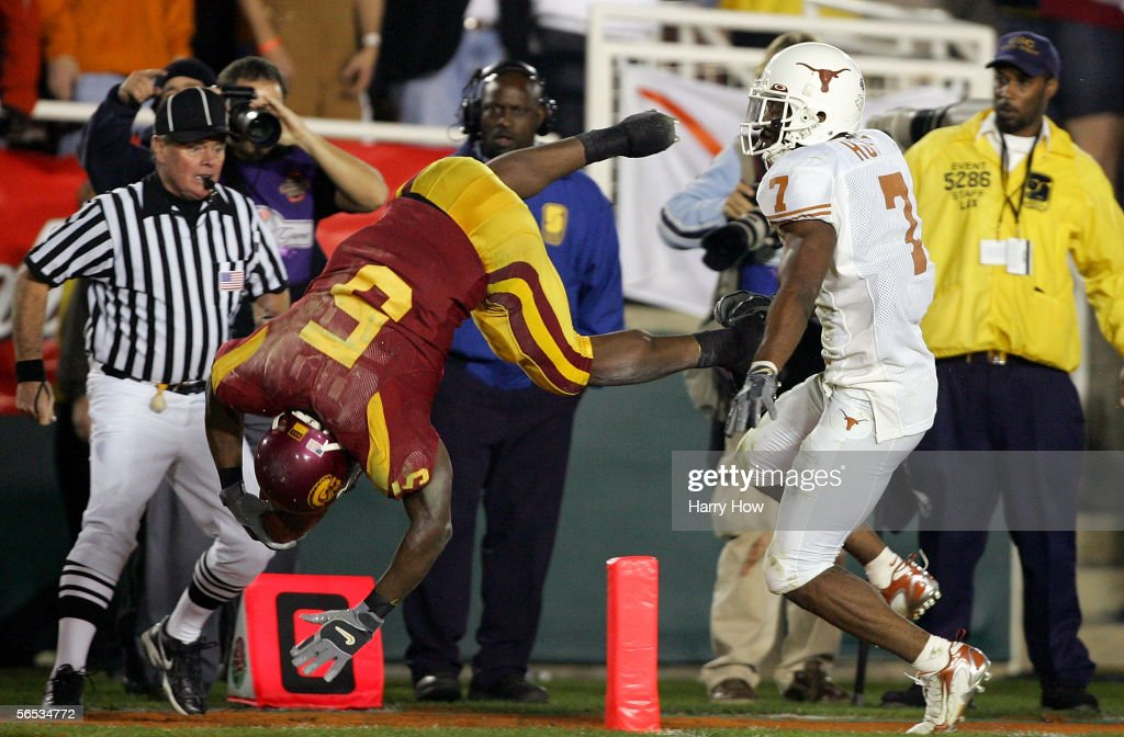 Reggie Bush #5 of the USC Trojans dives over Michael Huff #7 of the Texas Longhorns as he scores a 26 yard touchdown in the fourth quarter of the BCS National Championship Rose Bowl Game at the Rose Bowl on January 4, 2006 in Pasadena, California. Texas defeated USC