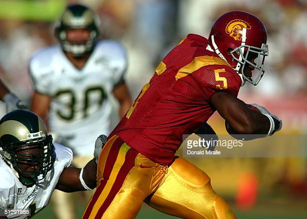 Reggie Bush of the USC Trojans runs against the defense of the Colorado State Rams on September 11 2004 during the first half at the Coliseum in Los...